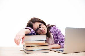 Tired woman in glasses sitting at the table with laptop and books. Looking at camera